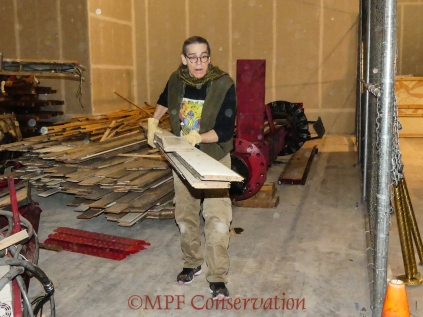 Mitchell moving ceiling boards; he stacked them against the wall for safety and stability.