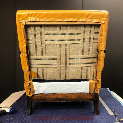 The outside back before upholstery, showing the jute webbing.